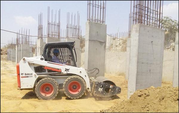 یک مینی لودر بابکت مشغول کار در یک پروژه ساختمانی با غلطک